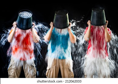 man pour a bucket of ice topped their head on a black background.