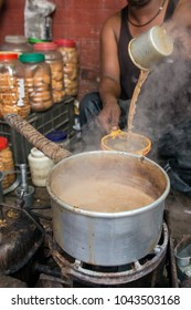 Man pour cup of hot milk tea Indian style or chai for customers in his shop along the street in Kolkata, India
