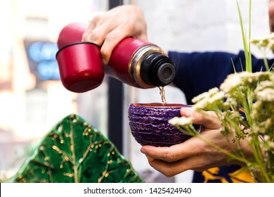 The man pour a herbal tea to handmade ceramic bowl