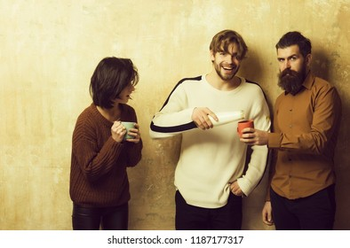 man pouring drink to bearded hipster and adorable girl or cute woman cups from bottle. Friends or people drinking milk or yogurt on beige background. Healthy dieting and lifestyle