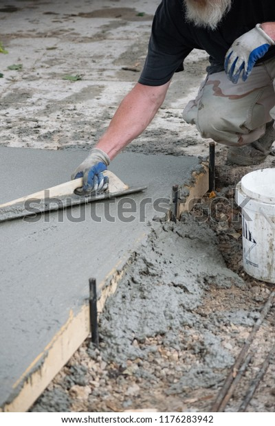 Man Pouring Finishing Concrete Driveway Stock Photo (Edit