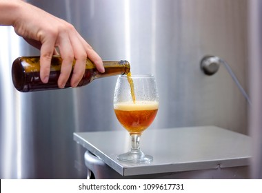 Man pouring fresh cold craft beer in glass, craft brewery concept , beer tasting