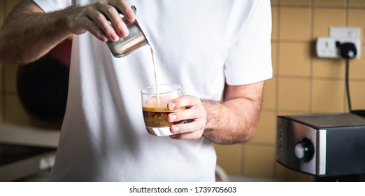 Man pouring frothed milk into espresso for making a latte cappuccino coffee. Home barista indoors lifestyle concept