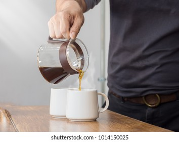 The man is pouring hot coffee from the coffee pot into the white coffee on the wooden table in the morning