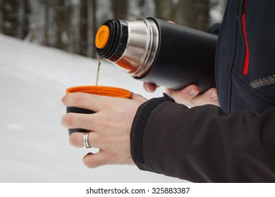 Man pouring hot tea from a vacuum flask (thermos) in the winter