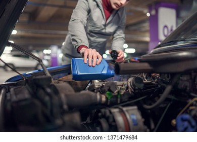 Man pouring oil in car with open hood