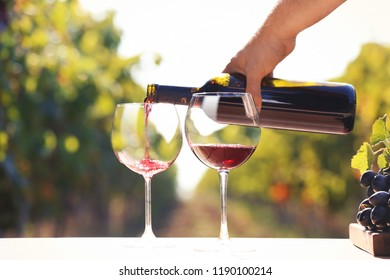 Man pouring red wine into glass on table outdoors