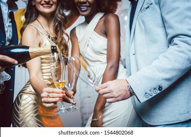 Man pouring sparkling wine into glass of his friends celebrating a party for new year or birthday