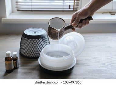 A man is pouring water into an aroma diffuser.