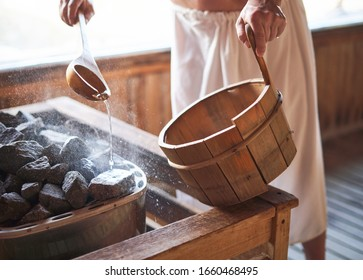 Man pouring water onto hot stone in sauna room. Steam on the stones, spa and wellness concept, relax in hot finnish sauna.