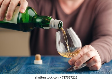 Man pouring whiskey himself in glass