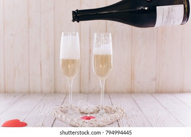 Man pours champagne in the glasses on white wooden table
