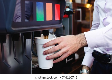 man pours a fizzy drink into a paper glass from a cola machine