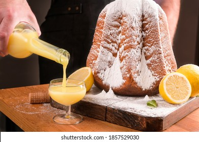 Man pours Limoncello in a glass on the table and a soft star-shaped pasta sprinkled with icing sugar. Traditional Italian pastries from Verona for Christmas with lemon, liqueur and vanilla.