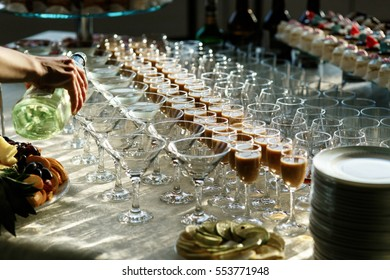 Man pours martini in cocktail glasses on dinner table
