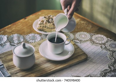 man pours milk into coffee