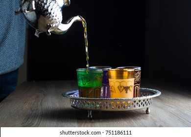 A man Pours Moroccan Tea  from Teapot into cups