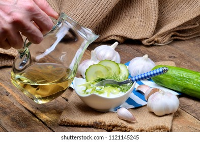 Man pours oil into Tzatziki - traditional Greek dressing or dip sauce, garlic, lemon, dill, cucumber, jug with oil, blue spoon and decoration in background