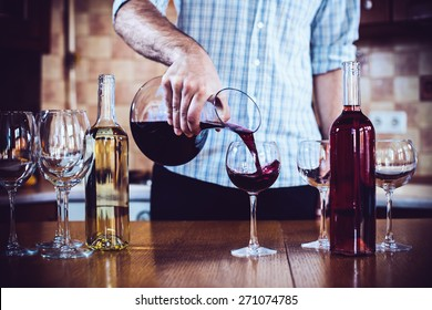 A man pours red wine from the decanter into a glass, home kitchen interior