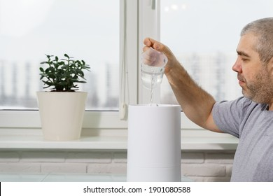 man pours water into a humidifier tank. using a humidifier at home
