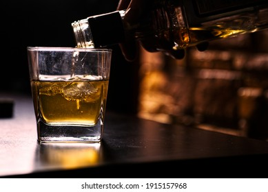 the man pours whiskey into a glass. American ice bourbon. Drink on the rocks