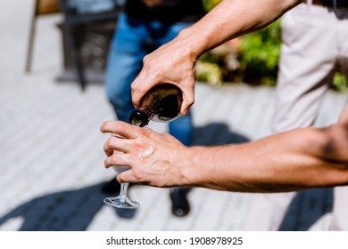 A man pours wine from a bottle into a glass.Hands close up