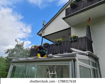 Man power washing conservatory roof and windows