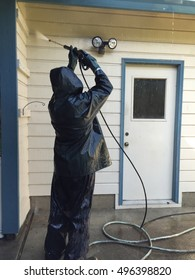 Man power washing a home to prepare it for a new paint job
