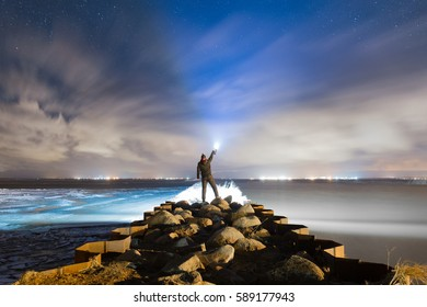 A man with powerful torch on the long pier in the starry night