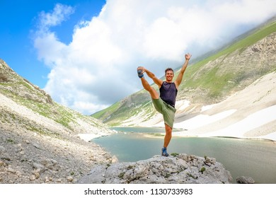 Man practice Yoga position over a big stone after a trekking to  high altitude lake (Pilato lake)  in the National Park of the Sibillini Mountains in Italy
