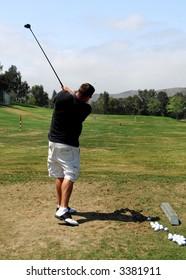 Man Practices at Golf Driving Range