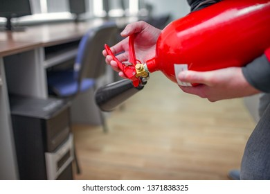 A man practices how to use a powder type extinguisher  in the office. The rescuer puts out the computer - Shutterstock ID 1371838325
