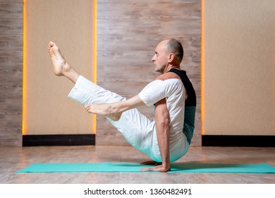 Man practices yoga while standing on hands on blue mat .