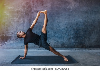 Man practicing advanced yoga against a urban background