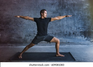 Man practicing advanced yoga against a dark wall