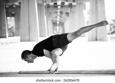 Man practicing advanced yoga in a urban background