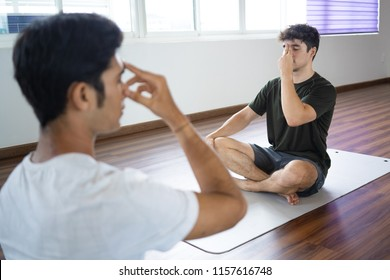 Man practicing alternate nostril breathing technique with personal instructor at yoga class. Guy sitting in sukhasana yoga pose. Pranayama concept.