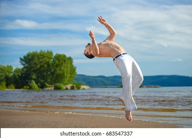 Man practicing capoeira on the beach - concept about people, lifestyle and sport. The man does the fighting element of capoeira.