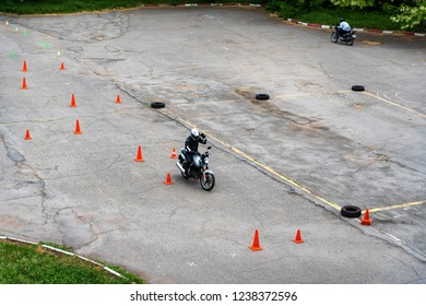 Man is practicing driving a motorcycle in a driving school