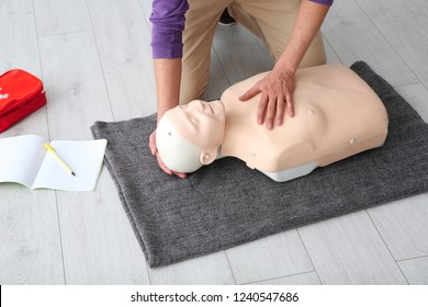 Man practicing first aid on mannequin  indoors, closeup