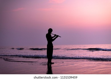 A man is practicing playing the flute on the birch in the sunset. GOA, India. 16.01.2018.