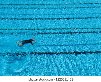 A man is practicing swimming alone in breaststroke style in a big swimming pool