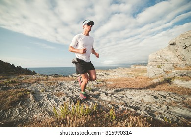 Man practicing trail running in a landscape of the coast