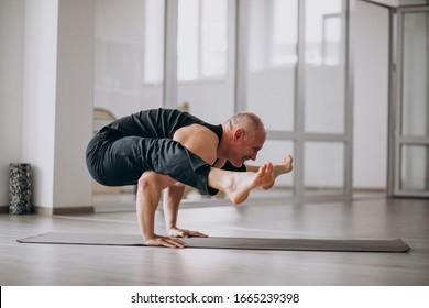 Man practising yoga in the gym