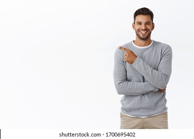 Man praising great concept, pointing left at your project as discuss corporate staff coworker. Attractive pleased businessman in grey casual sweater having chat and recommend check-out product