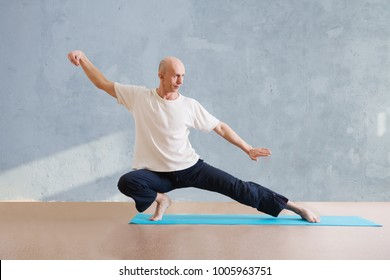 man praticing tai chi chuan in the gym. Chinese management skill Qi's energy. WU-SHU. Man practicing yoga.