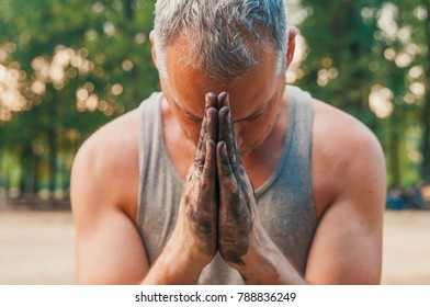 Man pray for god under heaven hope light : hope concept. Dirty hands clasped together for a prayer. Man praying with his head down and hands together, alone in nature