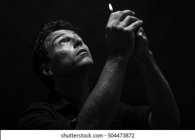 Man pray with a lighter in his hand. Low key , black and white portrait.