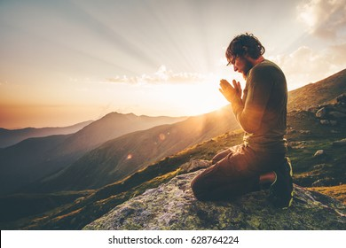 Man praying alone at sunset mountains Travel Lifestyle spiritual relaxation emotional concept vacations outdoor harmony with nature landscape