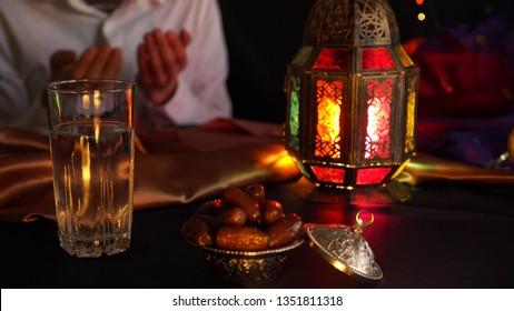 Man praying. Breaking the fast. Fasting the month of Ramadan. Iftar: the Daily Break Fast During Ramadan